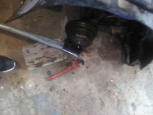 I used a cheater bar and socket and wedged it under the foot bar on the right side to break the left nut with a cheater bar and pipe wrench.