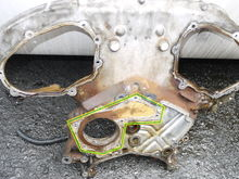 view of timing chain inner cover surface attaches to engine.  gasket or silicon sealant on surface within green-yellow marking.